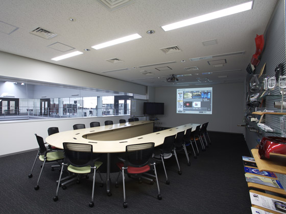 TAKUBO ENGINEERING CO., LTD./【Conference room】Conference room with a view of both the assembly factory floor and an office