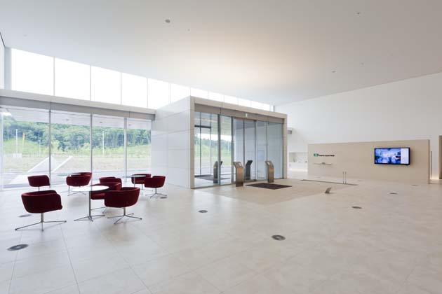 Tokyo Electron Miyagi Limited/【Entrance area】A simple entrance that is uniformly white. The bright red lobby chairs provide an accent.