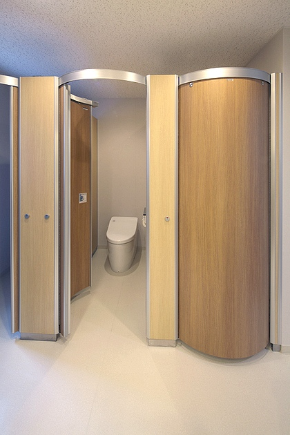 "FANCL Corporation/【Women's restroom】Tasteful wood-grain ""wavelet toilet booths"" are used."