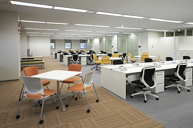 SGS Japan Inc./【Collaboration area】Meeting tables and family-restaurant-style benches are located next to windows with a scenic view.