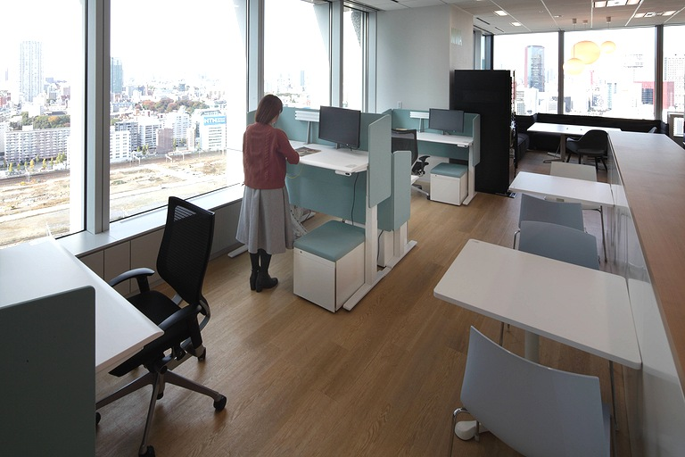 Tanseisha Co., Ltd./【Office area】In the open work space, height-adjustable desks can be used to change posture while working.